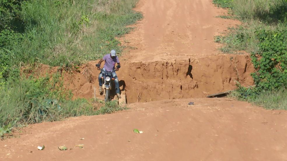 Mesmo com risco de queda, agricultor atravessa ponte danificada pelo rompimento das barragens.  — Foto: Rede Amazônica/Reprodução