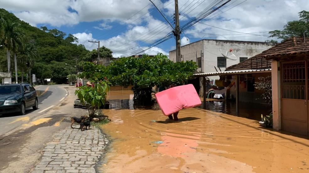 Moradores de Porciúncula retirando pertences das casas que foram atingidas pela cheia do Rio Carangola — Foto: João Brum/ Inter TV