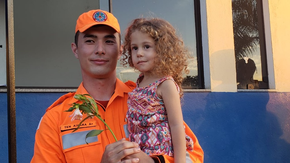 O tenente Pedro Aihara posa para fotos com menina durante homenagens que os bombeiros receberam de moradores e voluntários em Brumadinho — Foto: Raquel Freitas/G1