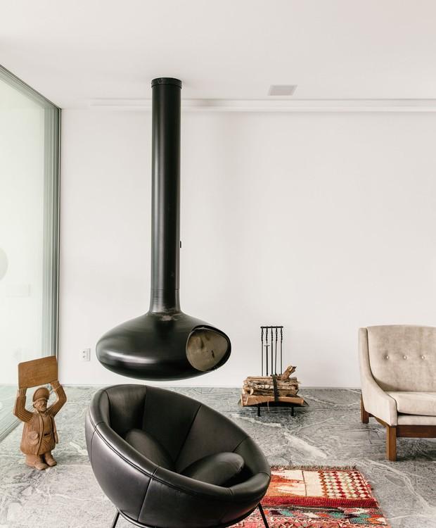A lareira preta e o tapete estampado oferecem detalhes mais rústicos ao ambiente (Foto: Stephan Ruiz/ Reprodução)