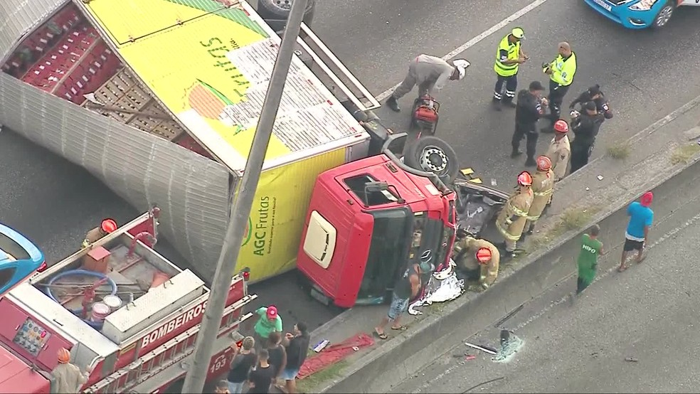 Caminhão que carregava frutas tombou sobre um carro na Avenida Brasil, altura de Irajá — Foto: Reprodução/ TV Globo