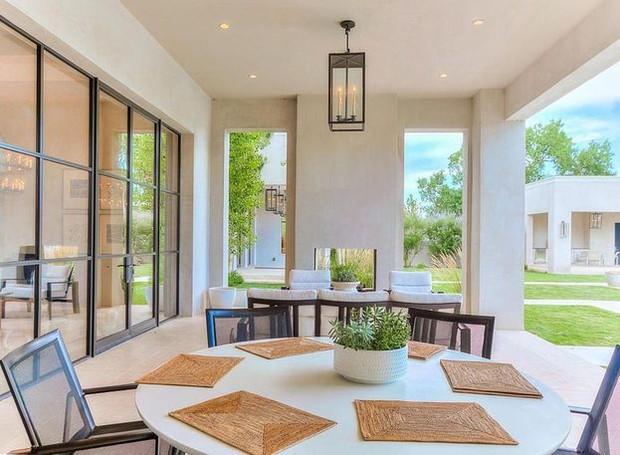 A área externa da casa inclui mesas e poltronas parar aproveitar o calor da cidade de Albuquerque (Foto: Realtor/ Reprodução)