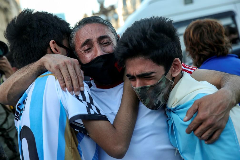 Senhor e dois jovens se abraçam e choram no adeus a Maradona em Buenos Aires — Foto: REUTERS/Ricardo Moraes