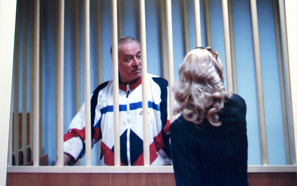 Sergei Skripal fala com sua advogada de trás das grades em uma corte em Moscou em foto de 9 de agosto de 2006 (Foto: AP Photo/Misha Japaridze, File)