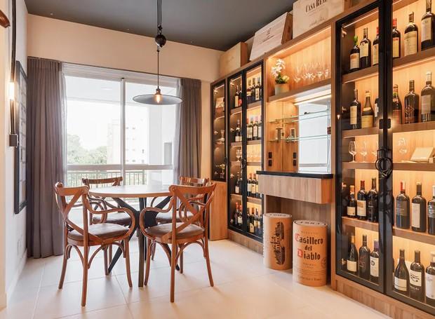 Banquetas que imitam rolhas ficam próximas à estante. Já o lustre de latão combina com as cadeiras de madeira simples e rústicas (Foto: Airbnb/ Reprodução)