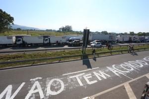 Manifestantes escrevem no asfalto da Dutra contra o acordo