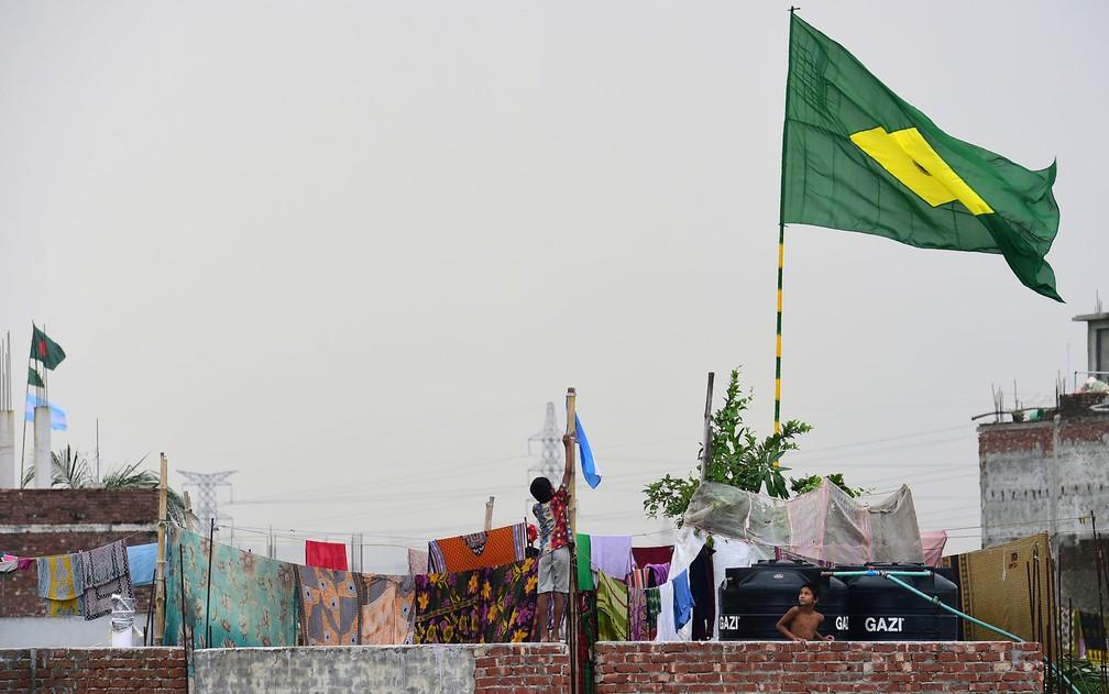 Criança pendura bandeira da Argentina perto de uma bandeira do Brasil em um subúrbio de Dhaka, em Bangladesh, em foto de 6 de junho (Foto: Munir Uz Zaman/AFP)