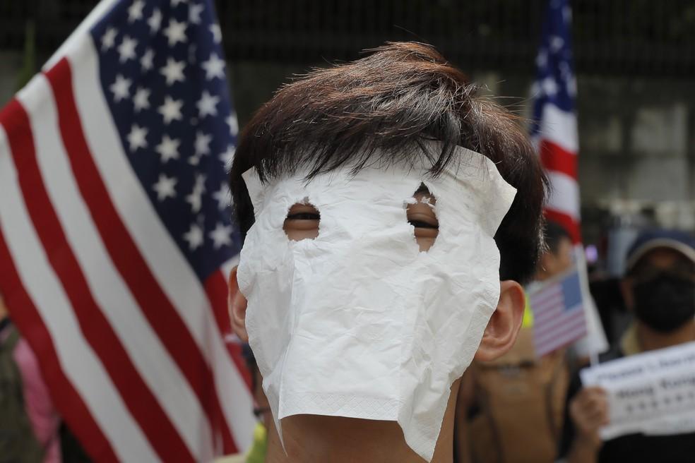 Manifestante cobre o rosto durante protesto em no consulado dos Estados Unidos em Hong Kong — Foto: AP Photo/Kin Cheung
