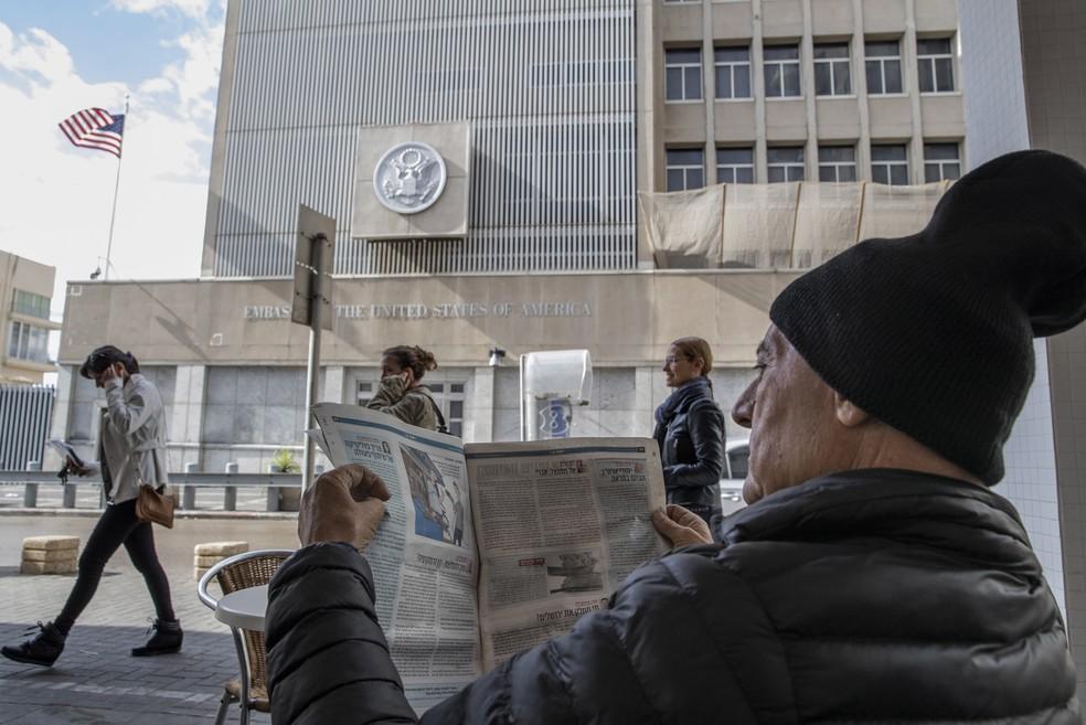 Homem lê jornal em café com embaixada americana em Tel Aviv à  sua frente (Foto: Reuters/Baz Ratner)