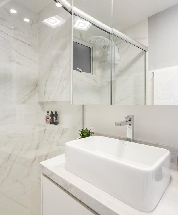 Tudo branquinho no banheiro - o espelho esconde um armário suspenso que guarda os itens do dia a dia (Foto: Eduardo Macarios/Divulgação)