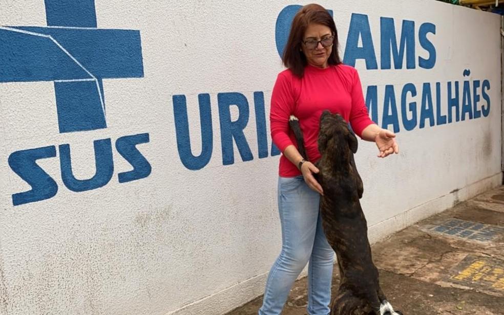 Cachorro que fica na porta de Cais pede carinho para a comerciante Maria Azevedo, em Goiânia, Goiás — Foto: Lis Lopes/G1