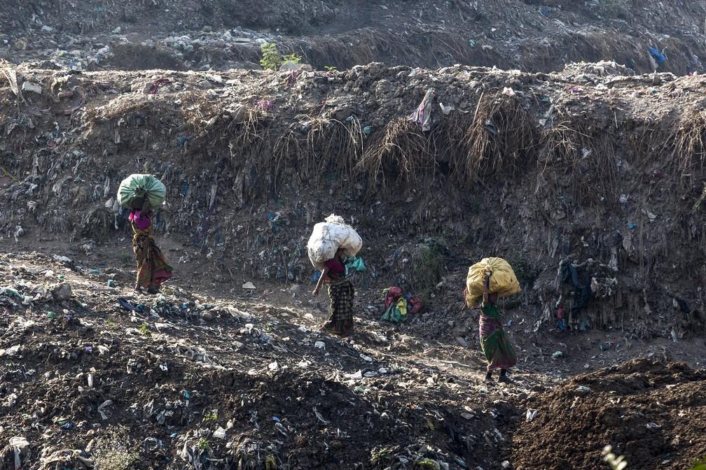 Moradores recolhem lixo de Ghazipur, o maior lixão de Nova Délhi. — Foto: Xavier Galiana/AFP