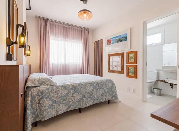 No quarto, quadros com rótulos e imagens de vinícolas decoram a parede (Foto: Airbnb/ Reprodução)