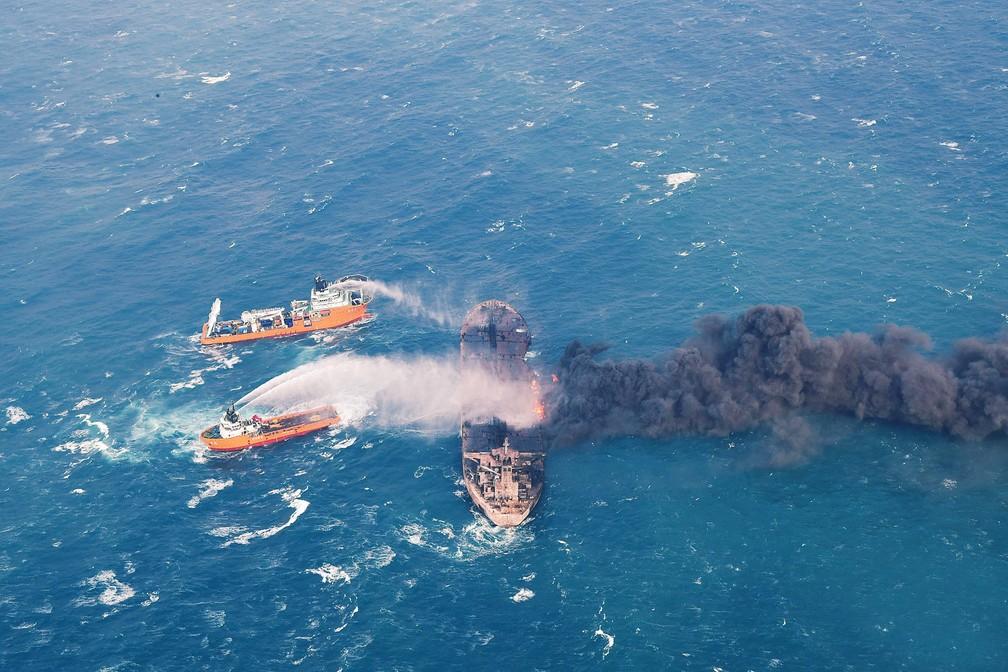 10 de janeiro - O navio de fornecimento chinês 'Shen Qian Hao' pulveriza espuma no petroleiro em chamas 'Sanchi', no mar da costa leste da China. As autoridades do país informaram que não foi detectado nenhum vazamento significativo, mas uma explosão obrigou a suspensão temporária do trabalho dos bombeiros (Foto: Ministério dos Transportes da China/Divulgação via AFP)