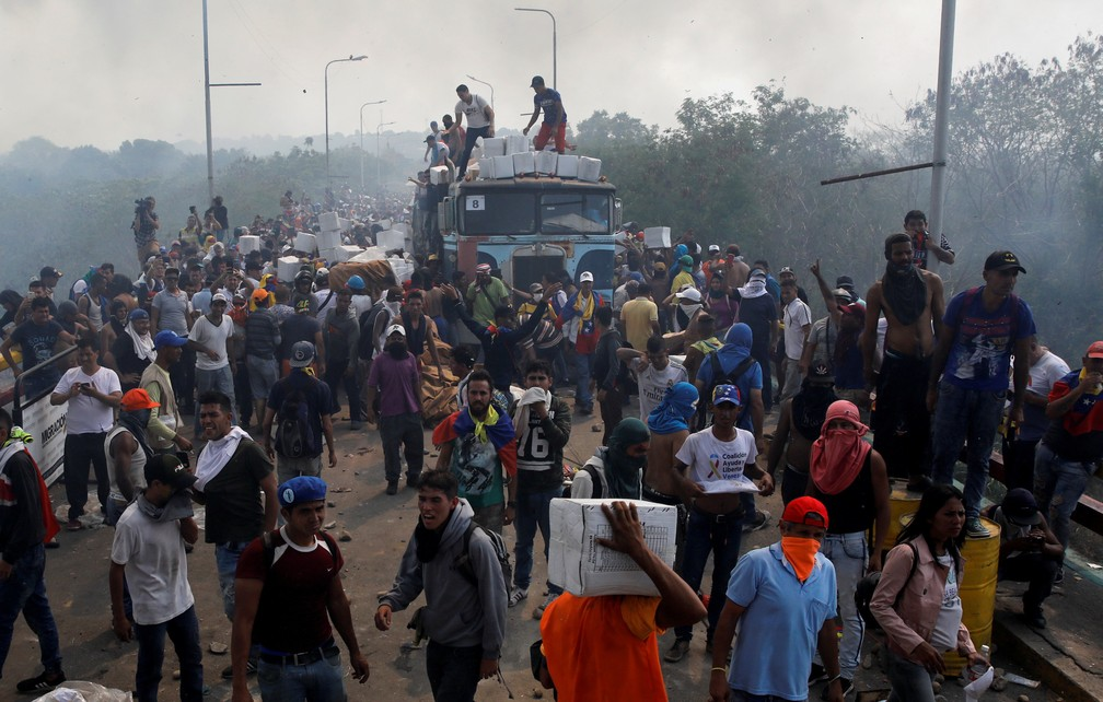 Pessoas ajudam na retirada dos alimentos que estavam no caminhão incendiado — Foto: Marco Bello/Reuters