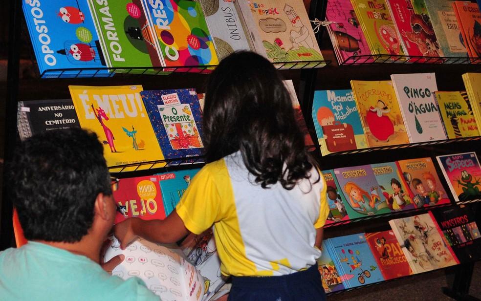 Criança olha livros infantis durante evento, em Brasília (Foto: Renato Araújo/Agência Brasília)