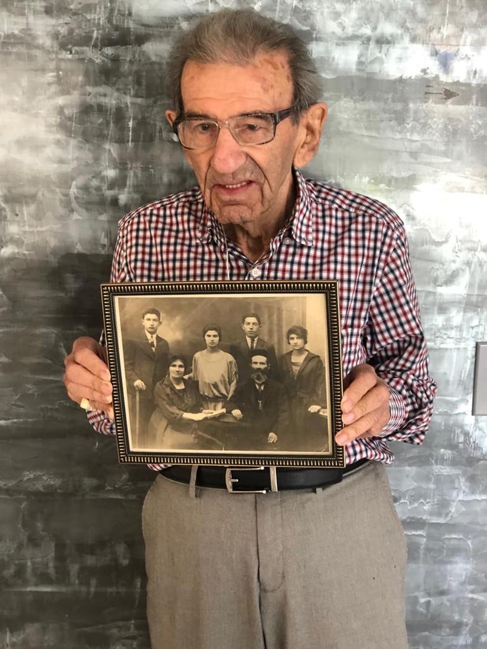 Saul segurando uma foto da família que perdeu no Holocausto. — Foto: Arquivo pessoal/Sylvia Kahana