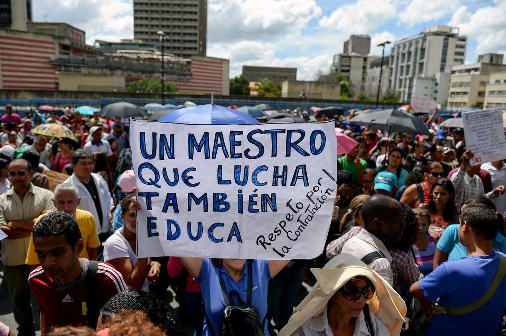 'Um professor que luta também educa', diz cartaz de manifestante em Caracas, na Venezuela — Foto: Federico Parra/AFP