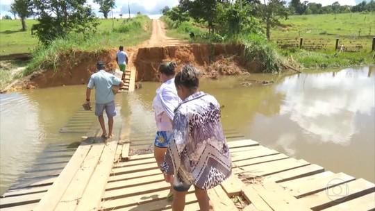 Moradores de área atingida por rompimento de barragens se arriscam em ponte danificada para buscarem comida em RO