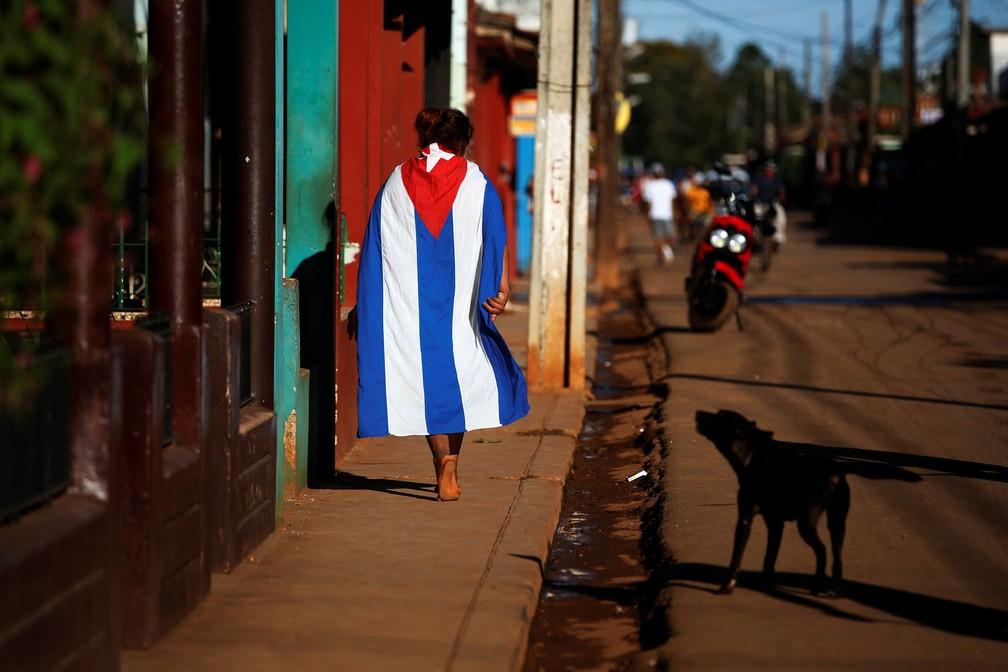 Um cachorro late para um homem enrolado em uma bandeira de Cuba na cidade de Alquizar — Foto: Tomas Bravo/Reuters
