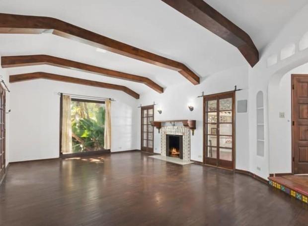 Uma lareira aquece a sala de entrada e troncos quadrados dão suporte ao teto (Foto: Hilton & Hyland/ Reprodução)