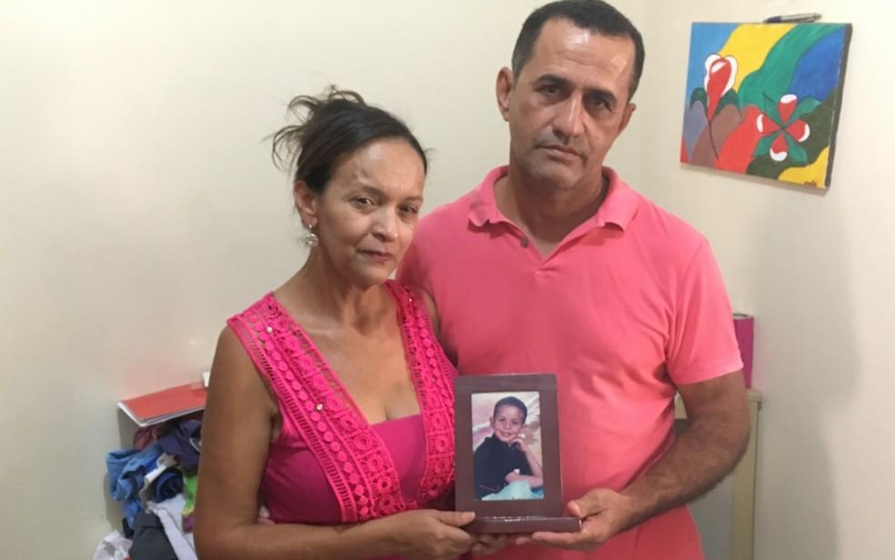 Idalira e o marido, Silvânio de Jesus, olham fotos do filho para aliviar a saudade  (Foto: Paula Resende/ G1)