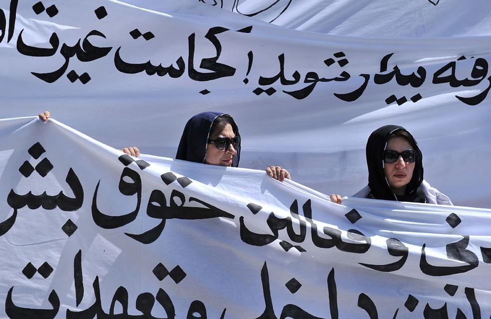 Em Cabul, mulheres afegãs marcham com bandeiras para protestar contra a execução pública de uma jovem por adultério — Foto: Massoud Hossaini/AFP