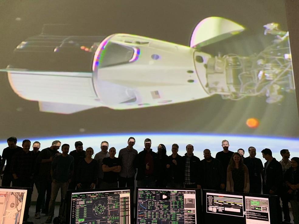 A equipe da SpaceX no posto de controle. Na imagem atrás, a Crew Dragon atracada à ISS. — Foto: Reprodução/Twitter (Elon Musk)