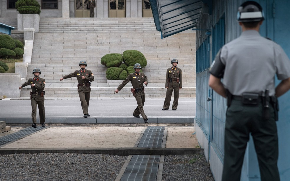 -  Soldados sul-coreanos e americanos na zona desmilitarizada que divide as duas Coreias. Ao fundo, militares do norte  Foto: AFP