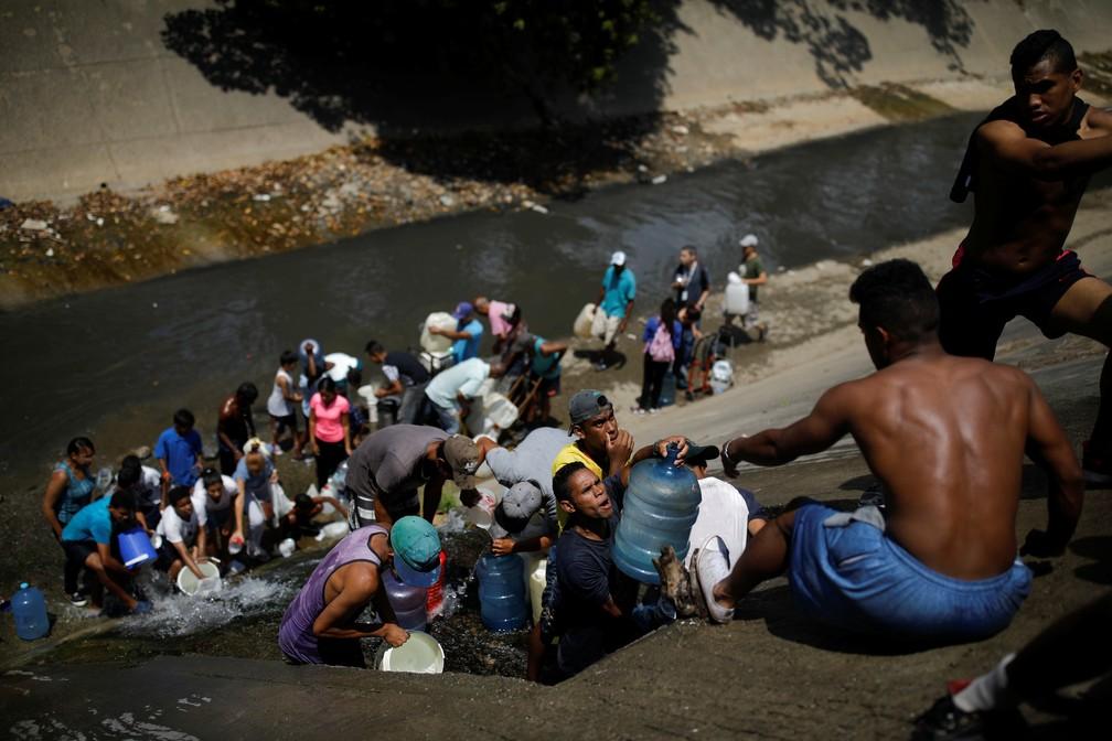 Moradores coletam esgoto no rio guaire, em Caracas, por não terem água em suas casas — Foto: Retuers/Carlos Garcia Rawlins