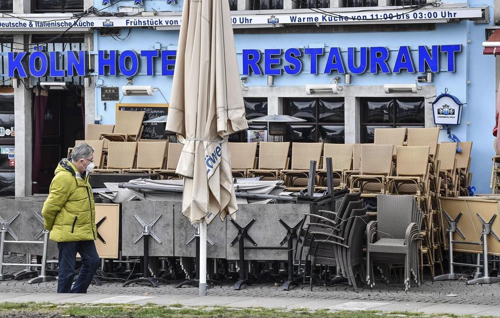 Pedestre passa por hotel e restaurante fechado na parte velha da cidade de Colônia, na Alemanha, nesta quinta-feira (18) — Foto: Martin Meissner/AP