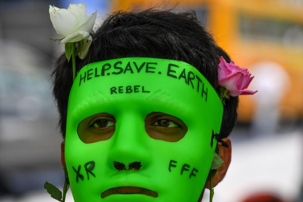 """Manifestante em Mumbai, na Índia, usa uma máscara verde-limão com os dizeres """"ajude a salvar a Terra"""" para pedir a preservação da Amazônia durante protesto em frente ao consulado brasileiro nesta sexta-feira (23).  — Foto: Indranil Mukherjee/ AFP"""