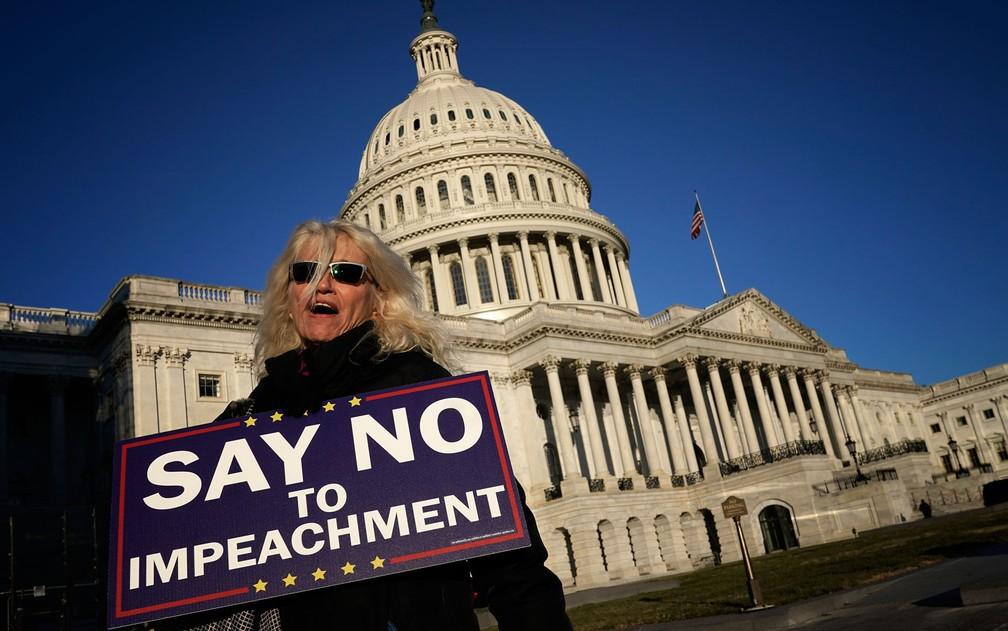 Apoiadora do presidente Donald Trump exibe cartaz contra o impeachment, em frente ao Capitólio, em Washington, na quarta-feira (18) — Foto: Win McNamee/Getty Images/AFP