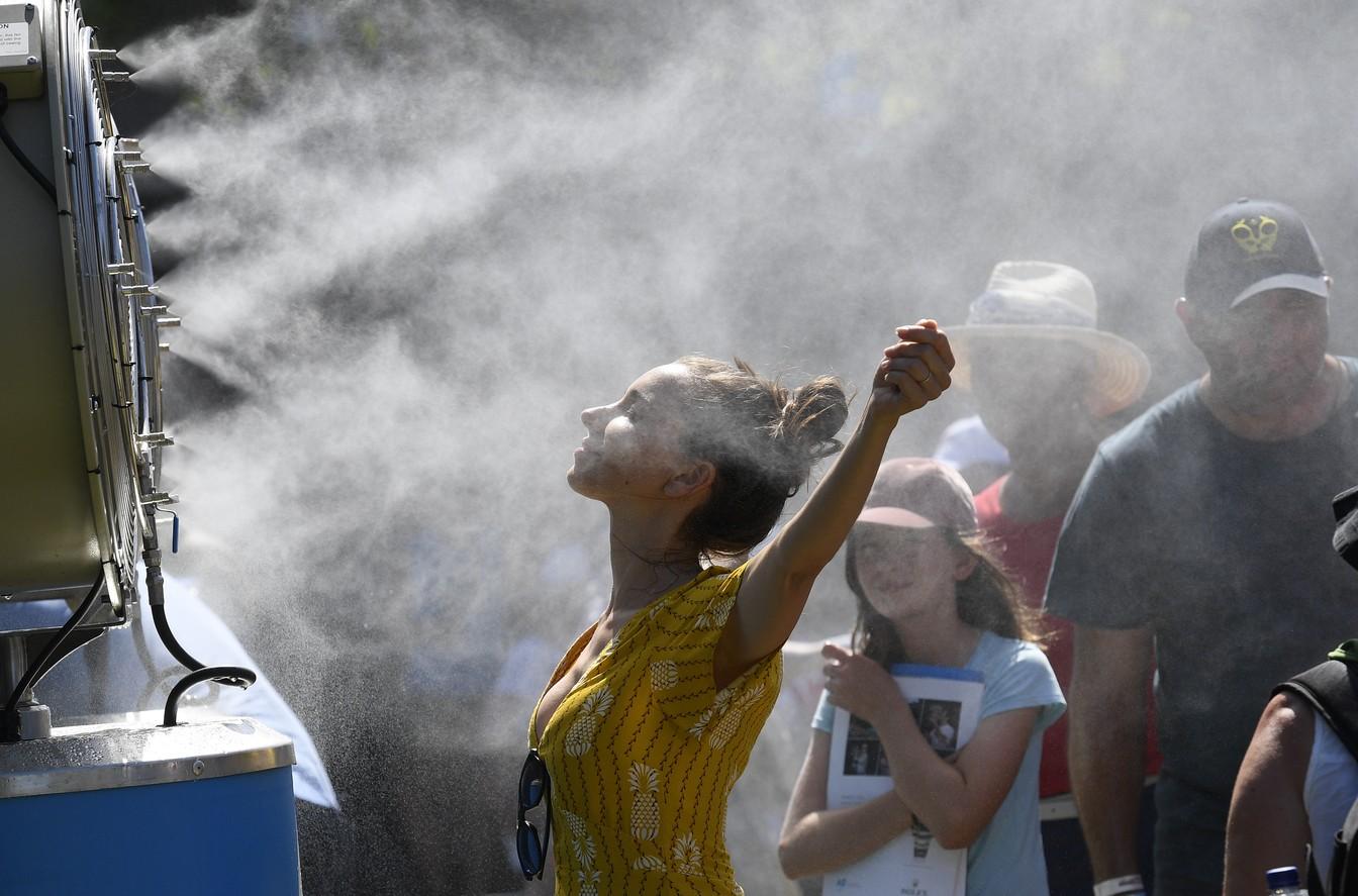 Foto de arquivo mostra mulher se refrescando durante o torneio Aberto da Austrália — Foto: AP Photo/Andy Brownbill