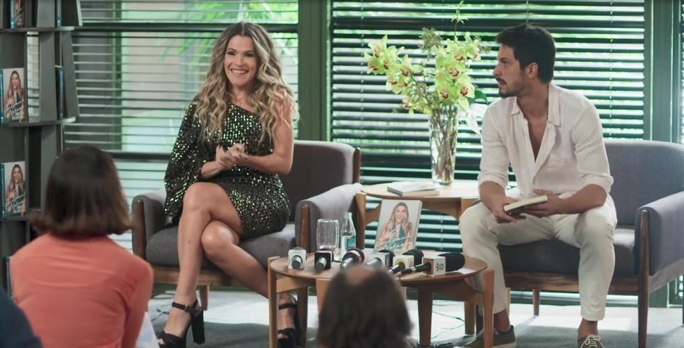 Silvana Nolasco (Ingrid Guimarães) e Marcos (Romulo Estrela) durante a coletiva de imprensa sobre o livro dela em 'Bom Sucesso' — Foto: Globo