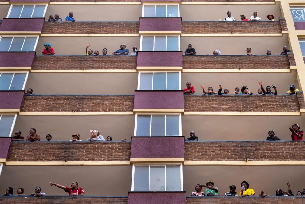 Moradores do povoado de Hillbrow, no centro de Joanesburgo, na África do Sul, acenam de suas varandas durante isolamento para impedir que o coronavírus se espalhe — Foto:  Jerome Delay/AP