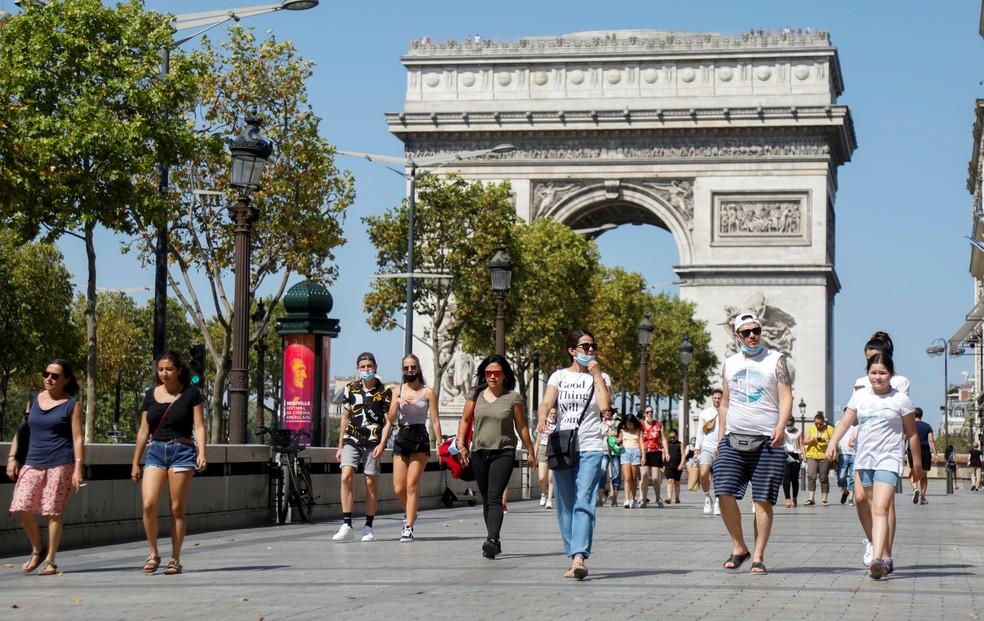 Pessoas caminham na Champs-Elysees, perto do Arco do Triunfo, em Paris, nesta quarta-feira (12), enquanto a França reforça o uso de máscara como parte dos esforços para conter o ressurgimento da Covid-19 no país — Foto: Charles Platiau/Reuters