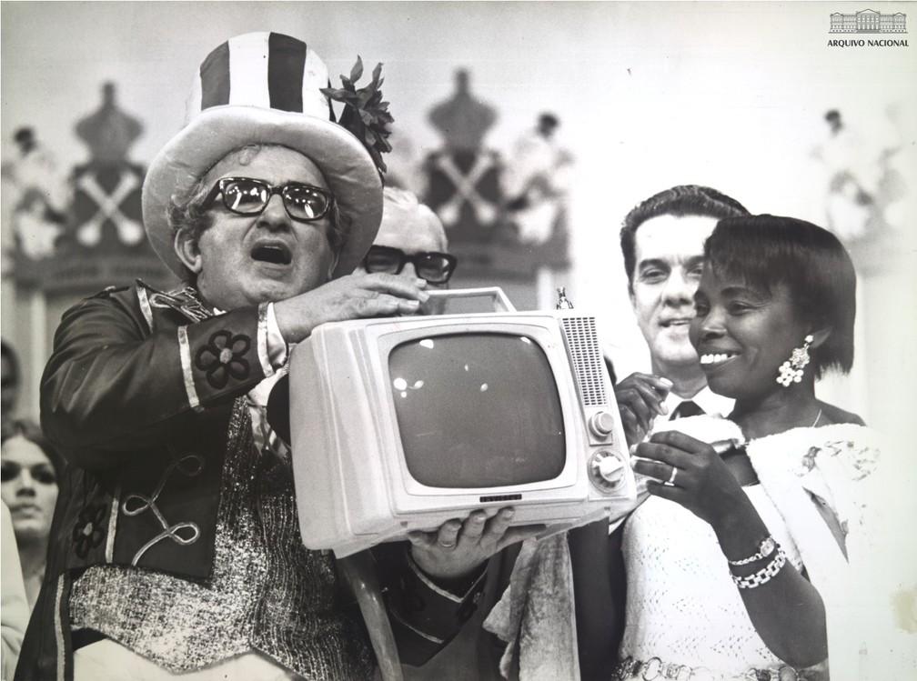 O Velho Guerreiro e os calouros: Chacrinha entregando aparelho de televisão para a vencedora da disputa de melhor calouro da noite — Foto: Arquivo Nacional