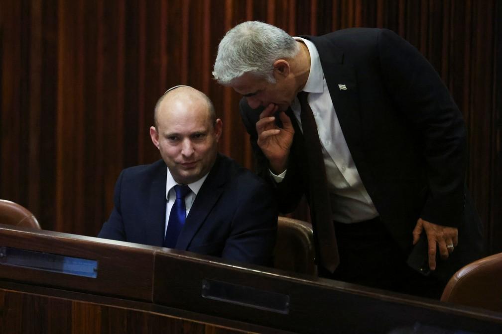 Sentado, Naftali Bennett fala com Yair Lapid durante sessão no Parlamento Israelense nesta quarta (2). Os dois devem se revezar no comando do governo de Israel, caso os parlamentares ratifiquem a coalizão — Foto: Ronen Zvulun/Reuters