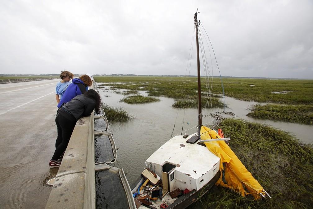 Moradores observam barco a vela que se soltou em Isle of Palms, na Carolina do Sul, nesta quinta-feira (6) — Foto: AP/Mic Smith