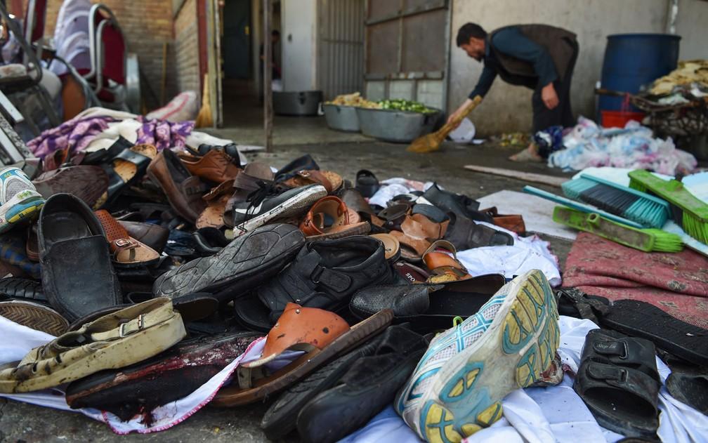 Homem limpa área ao lado de pilha de sapatos e sandálias de vítimas — Foto: Wakil Kohsar / AFP Photo