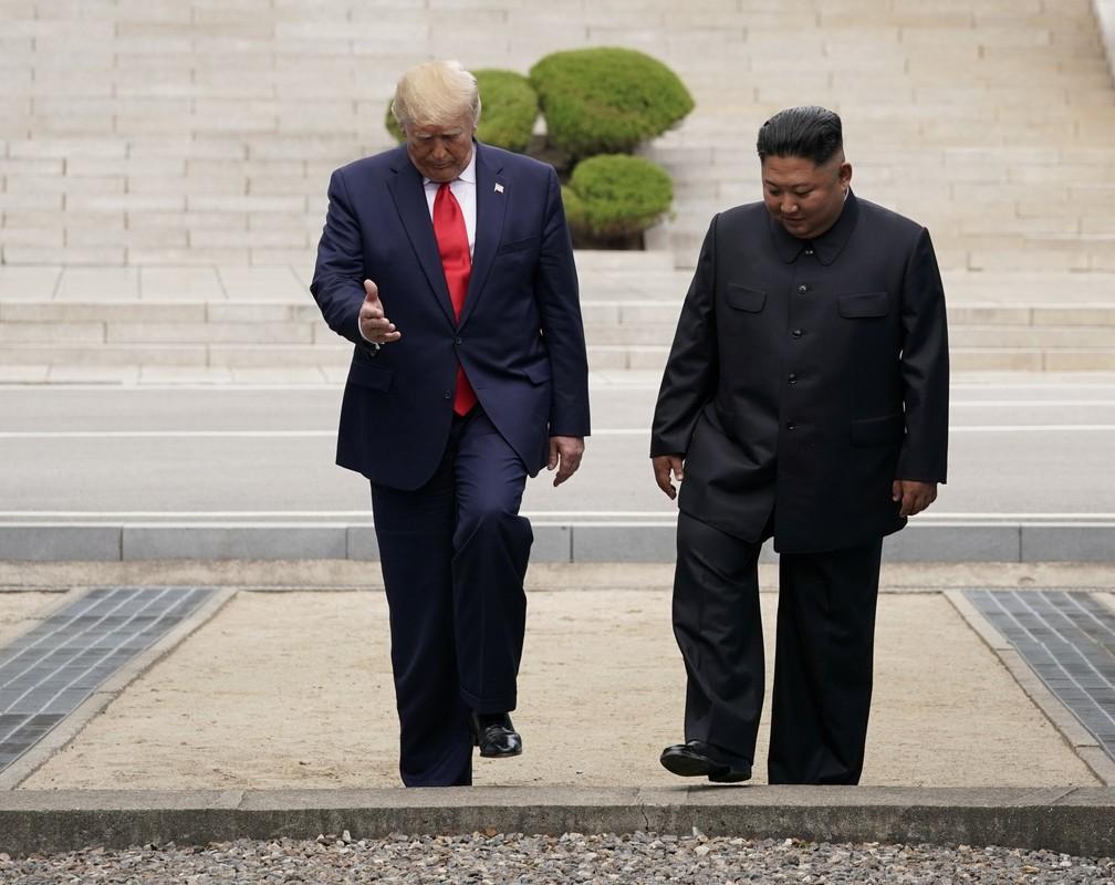 Donald Trump e Kim Jong-Un deram alguns passos, juntos, no território da Coreia do Norte, neste domingo (30). — Foto: Kevin Lamarque/Reuters