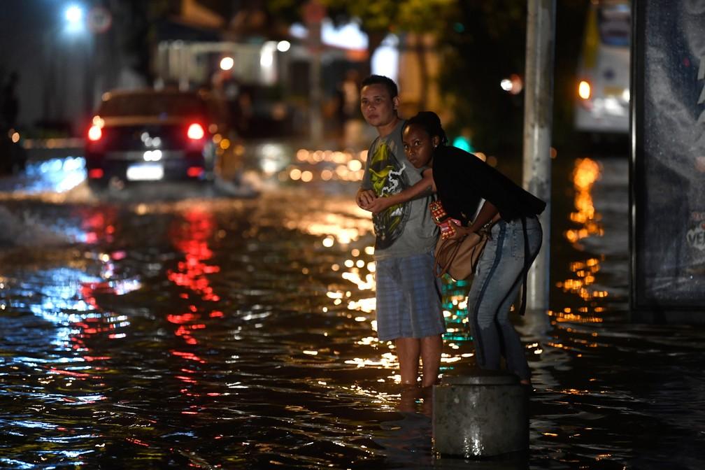 Pessoas aguardam por ônibus em uma rua alagada durante temporal na noite de quarta-feira (6) no Rio de Janeiro — Foto: Mauro Pimentel/AFP