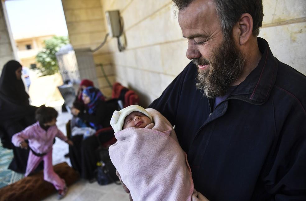 Homem que foi usado pelo Estado Islâmico como escudo humano junto com sua família segura bebê recém-nascido após fugir do centro de Raqa, na Síria (Foto: Bulent Kilic / AFP )