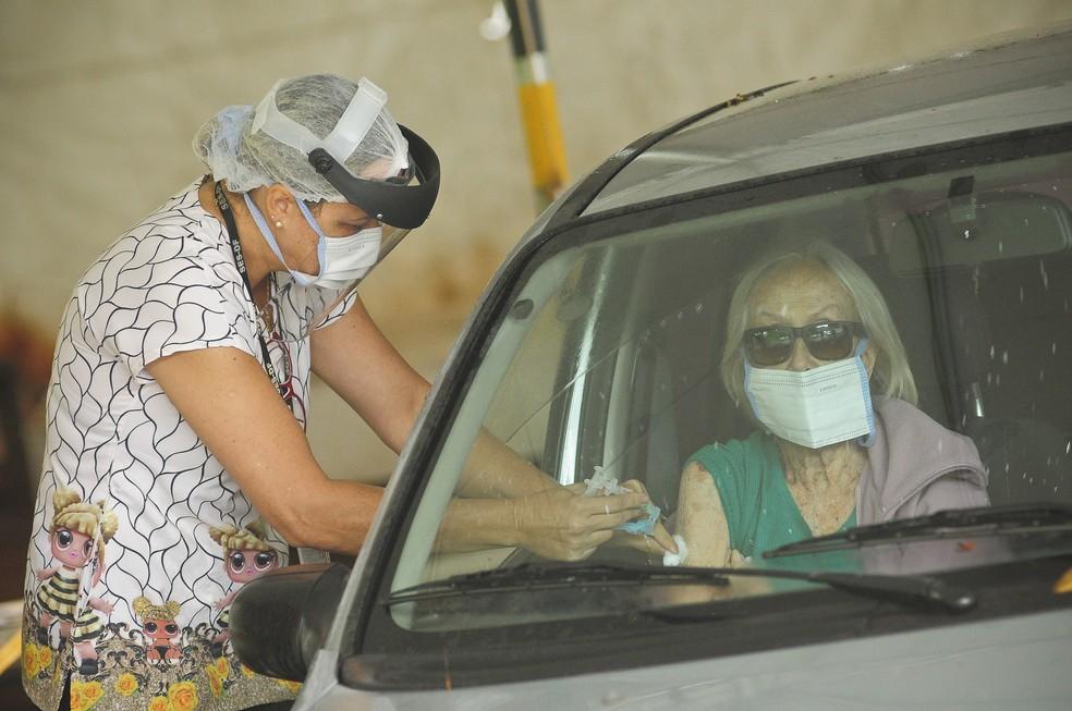 Servidora aplica vacina contra a gripe em idosa, dentro do carro, no Distrito Federal — Foto: Breno Esaki / Secretaria de Saúde