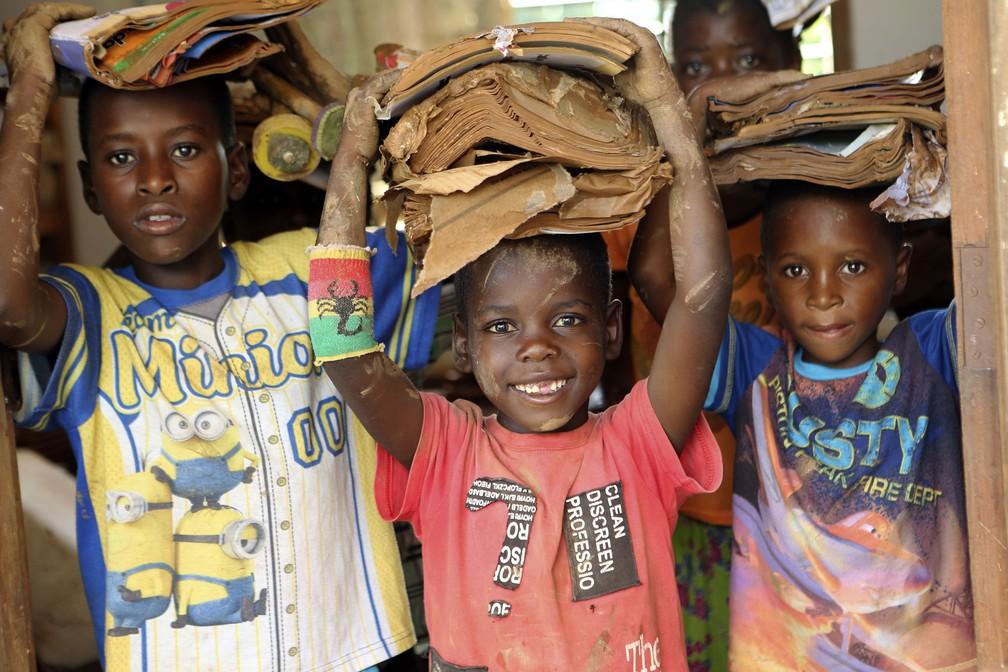 Crianças carregam livros sujos por alagamentos causados pelo ciclone Idai em Moçambique — Foto: Tsvangirayi Mukwazhi/AP Photo