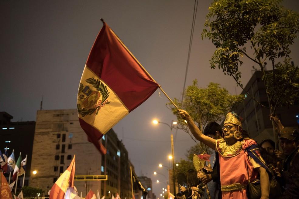 Apoiador do presidente peruano, Martin Vizcarra, agita a bandeira em manifestação perto do Congresso, na segunda-feira (30)  — Foto: Rodrigo Abd/AP