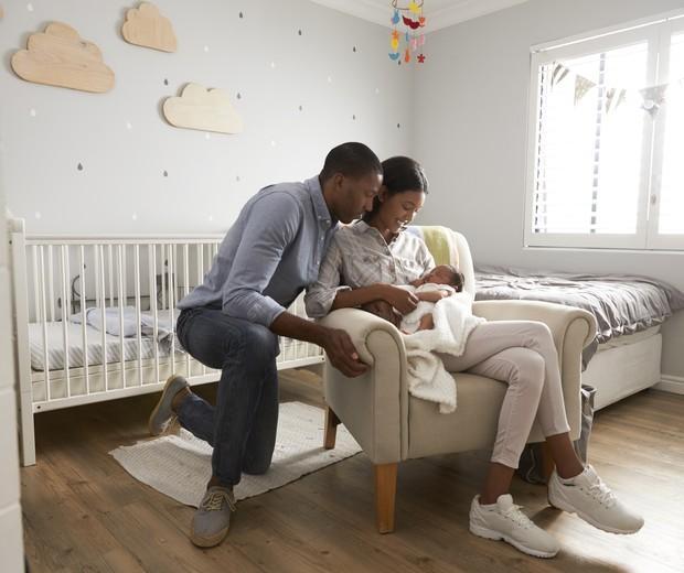 Pai e mãe carregando o filho recém-nascido no colo (Foto: Thinkstock)