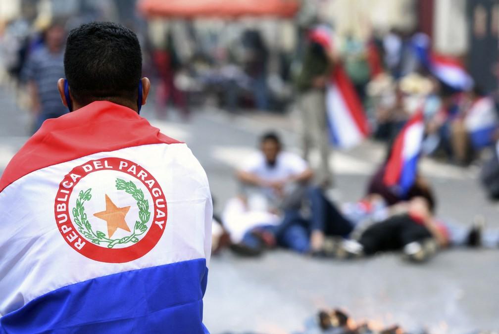 Manifestantes usam bandeiras do Paraguai em atos contra o presidente Mario Abdo nesta quarta-feira (17) — Foto: Daniel Duarte/AFP
