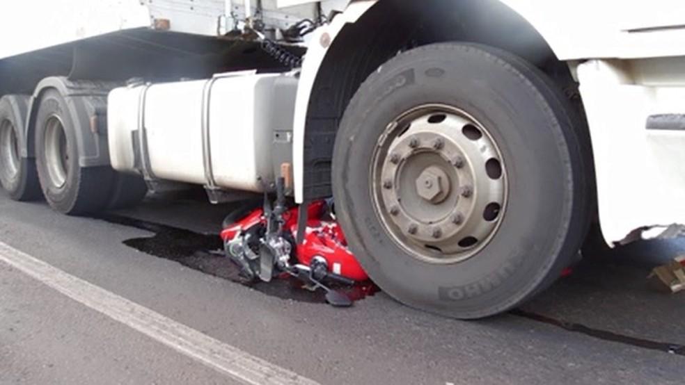 Moto parou embaixo de um dos rodados de caminhão em Maringá — Foto: Reprodução/RPC